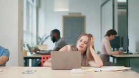 Чувство молодой женщины сонное на coworking Буря дама пробуя работать на ноутбуке видеоматериал