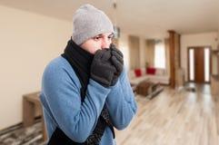 Чувство молодого человека холодное и грея его руки Стоковая Фотография