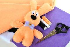Чувствуемый бежевый кролик Handmade мягкая игрушка, поток, ножницы на войлоке пурпура Стоковая Фотография RF