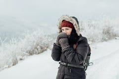 Чувствуя холод - женщина одела теплый дуть на ее руках Стоковое Изображение