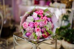 Чудесный букет розовых пионов роз, фиолетовых и белых украшенных с зелеными листьями Стоковые Фотографии RF