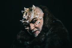 Чужеземец, демон, состав знахаря Концепция ужаса и фантазии Человек с терниями или бородавочками в меховой шыбе Демон на черноте стоковые изображения