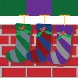 Чулки рождества вися на каминной доске камина бесплатная иллюстрация