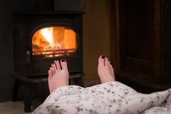 Чуть-чуть ноги женщины уютным камином Женщина ослабляет теплой елью стоковая фотография rf