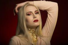 Чудесная молодая женщина с совершенным составом в красном цвете и золоте Стоковые Изображения