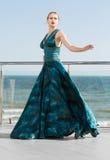 Чудесная элегантная дама в длинном развевая изумрудном платье, представляя около яркого голубого моря Красивая девушка на каникул стоковые изображения