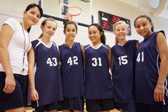 Члены женской баскетбольной команды средней школы с тренером Стоковая Фотография