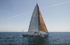 Члены команды сидя на стороне парусника в океане Стоковые Изображения RF