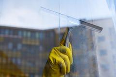 Шабер для моя окон в руках в желтых перчатках Стоковые Фото