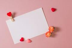 Шаблон канцелярских принадлежностей/фото с струбциной, цветками весны и малыми сердцами на свете - розовой предпосылке Стоковое фото RF