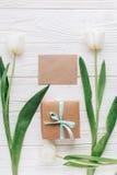 Шаблон поздравительной открытки с стильными присутствующими коробкой и тюльпанами на w Стоковые Фотографии RF