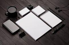 Шаблон фирменного стиля, пустые канцелярские принадлежности установил с кофе и наушником на черной стильной деревянной предпосылк Стоковые Изображения RF