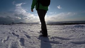 Шаги в снег вдоль моря в медленном mo видеоматериал