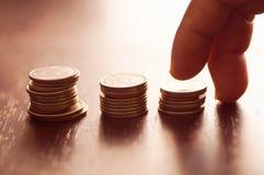 Шаг пальца дальше штабелированный денег монетки, концепции внутри растет и идет шаг за шагом Стоковое Изображение