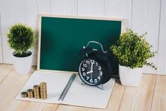Шаг стогов и будильника монеток с зеленой доской, примечанием Стоковая Фотография RF