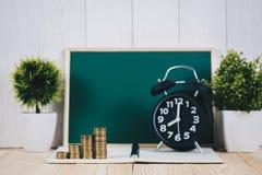 Шаг стогов и будильника монеток с зеленой доской, примечанием Стоковые Фото