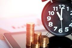 Шаг стогов и будильника монеток с планшетом и fi Стоковая Фотография