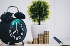 Шаг стогов и будильника монеток, тетради и финансового gra Стоковые Фото