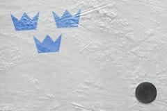 Шайба хоккея и изображение шведского символа на льде th стоковое фото