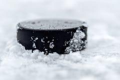 Шайба хоккея лежит на конце-вверх снега стоковая фотография rf