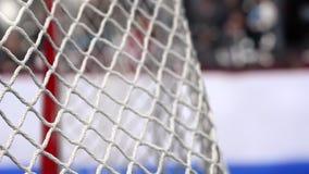 Шайба хоккея летает в сеть на досках хоккея с голубой нашивкой В начале движения ускорено ход после этого медленно