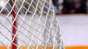 Шайба хоккея летает в сеть на досках хоккея с желтой нашивкой В начале движения ускорено ход после этого медленно