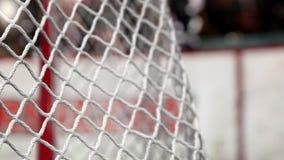 Шайба хоккея летает в сеть на досках хоккея с красной нашивкой В начале движения ускорено ход после этого медленно