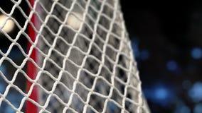 Шайба хоккея летает в сеть на стадионе с желтыми и голубыми светами В начале движения ускорено ход после этого медленно