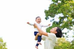 Шаловливая азиатская мать бросая вверх счастливый ребенка в саде природы Мать поднимаясь вверх по сыну на парке стоковые изображения
