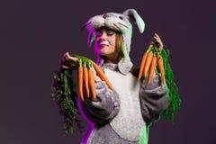 Шаловливая девушка в полном костюме зайчика тела с морковами Стоковые Фото