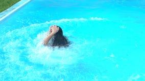 Шаловливая девушка делая воду взорвать скачку в бассейн, имеющ потеху, воссоздание акции видеоматериалы