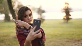 Шаловливая девушка расчесывая волосы на смартфоне в парке осени акции видеоматериалы