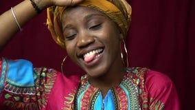Шаловливая чернокожая женщина в традиционных африканских одеждах представляя с ее языком вне, стрельба замедленного движения акции видеоматериалы