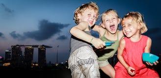 Шаловливые дети играя и представляя смешно на заграждении Марины, Сингапуре стоковое фото rf