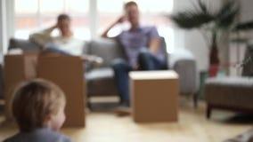 Шаловливые счастливые дети играя игру держа коробки на двигая день сток-видео