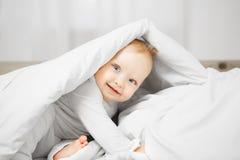 Шаловливый младенец сидит на кровати и прячет под прикрытым теплым Стоковые Изображения