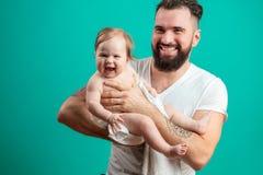 Шаловливый отец нося его усмехаясь младенческого ребенка на шеи над голубой предпосылкой стоковая фотография
