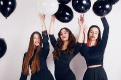 Шальное время партии 3 красивых стильных женщин в платье элегантного вечера вскользь черном празднуя, имеющ потеху, танцуя Стоковое Изображение RF