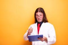 Шальной мужской доктор смотря смешной к доске сзажимом для бумаги стоковое фото rf