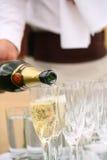 Шампанское кельнера лить в стеклах на таблице стоковое изображение