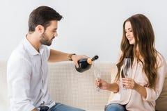 шампанское молодого человека лить в стекло пока сидящ на кресле с девушкой стоковое изображение rf