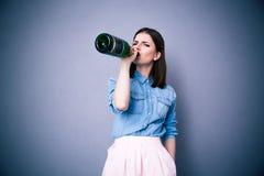 Шампанское молодой женщины выпивая от бутылки Стоковое Изображение
