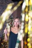 Шампанское привлекательной женщины выпивая на партии ` s Нового Года Стоковые Фотографии RF