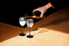 Шампанское человека лить в стекло на некоторых праздничных событии или приеме по случаю бракосочетания Стоковое Изображение