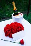 Шампань и розы с примечанием Стоковые Изображения