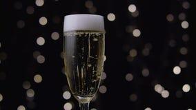 Шампань льет вне белую пену через края стекла нот bokeh предпосылки замечает тематическое сток-видео