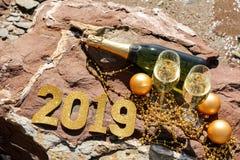 Шампань на каменистом пляже морем, Новый Год празднует концепцию подготовки Стоковое Изображение