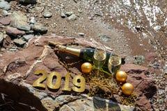 Шампань на каменистом пляже морем, Новый Год празднует концепцию подготовки Стоковая Фотография