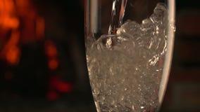 Шампань полита в стекло на предпосылке огня видеоматериал