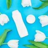 Шампунь, сливк и белые тюльпаны цветут на голубой предпосылке Блог красоты Плоское положение, взгляд сверху Стоковое фото RF
